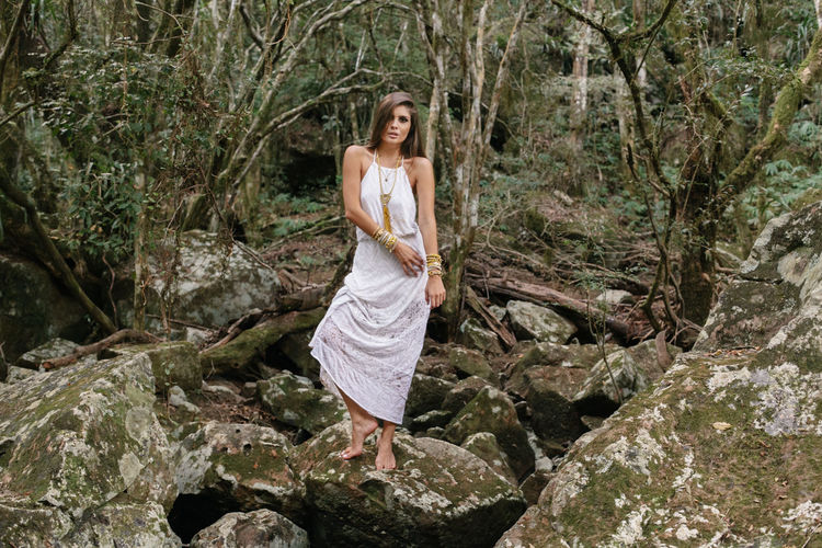 Portrait Of Young Woman Standing On Rock In Forest