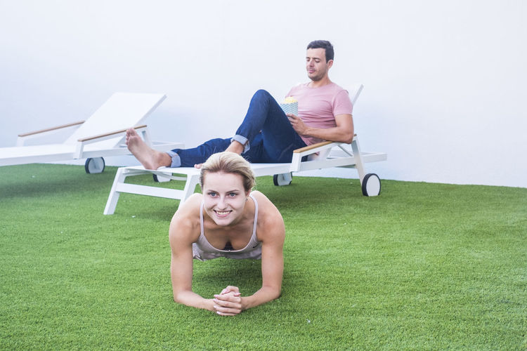 Portrait of woman exercising with man relaxing on chair in background