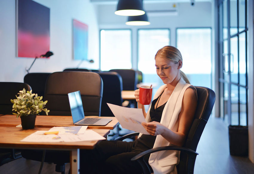 Business blonde girl drinking a cup of coffee and reading a business document Blonde Meeting Office Working Adult Blond Hair Business Business Woman Businesswear Communication Day Flower Indoors  Meeting Room Occupation Office One Person One Young Woman Only Paperwork People Real People Table Technology Using Laptop Western Wireless Technology Women Working Young Adult Young Women