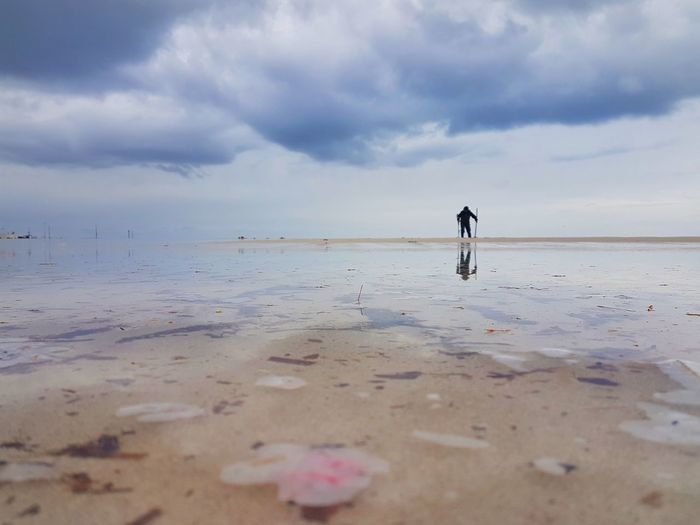 Silhouette person standing at beach against cloudy sky