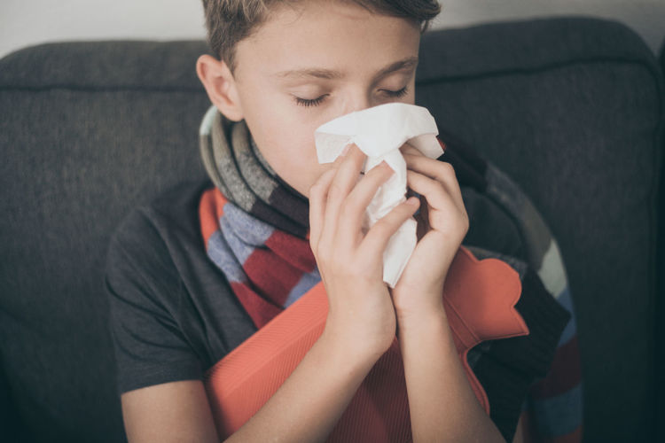 Close-up of boy blowing nose while sitting on sofa
