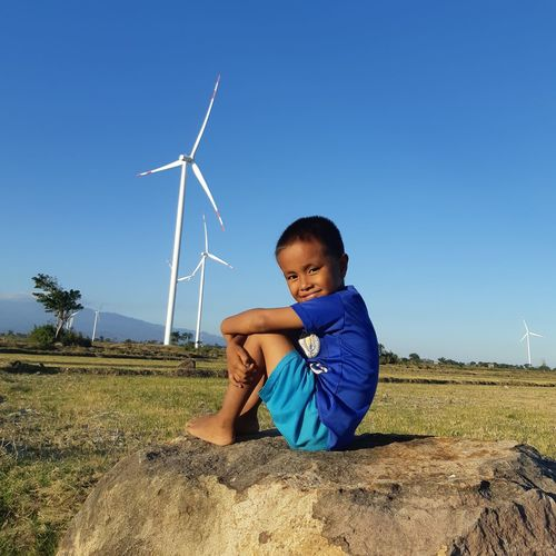 Boy on field against clear blue sky