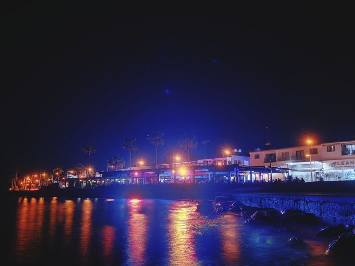 Illuminated pier over sea against sky at night