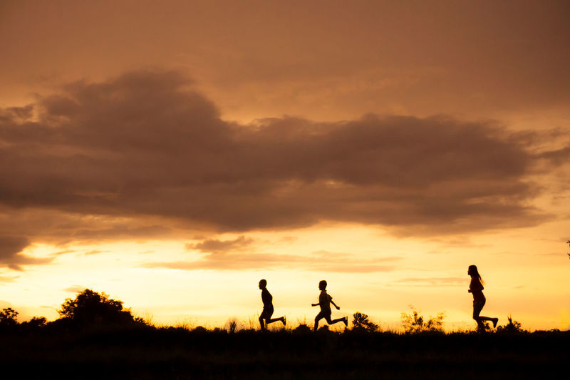 Silhouette People Running On Field Against Sky During Sunset