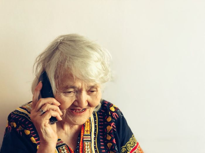 Close-Up Of Senior Woman Talking On Phone By White Wall