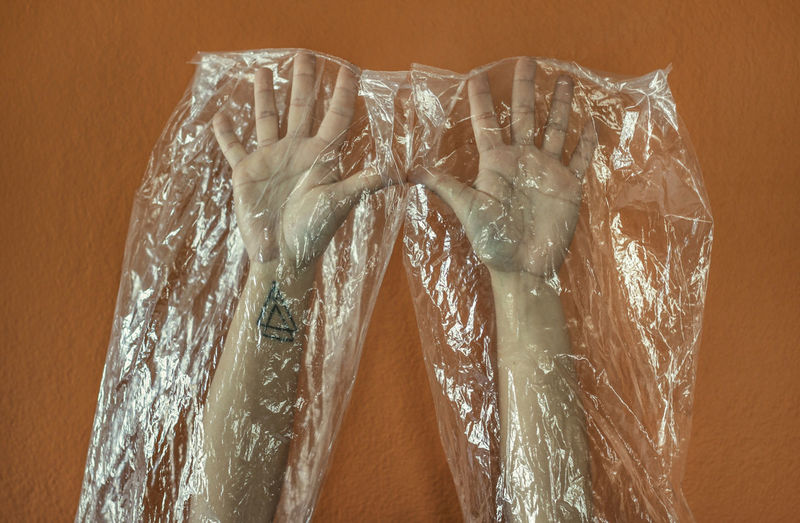 Close-up of hands covered with plastic bag