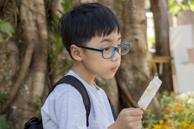 Black Hair Boys Childhood Concentration Day Elementary Age Eyeglasses  Focus On Foreground Headshot Holding Leisure Activity Lifestyles Nature One Boy Only One Person Outdoors People Real People Tree