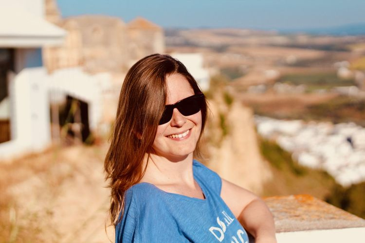 Portrait of smiling woman wearing sunglasses in city