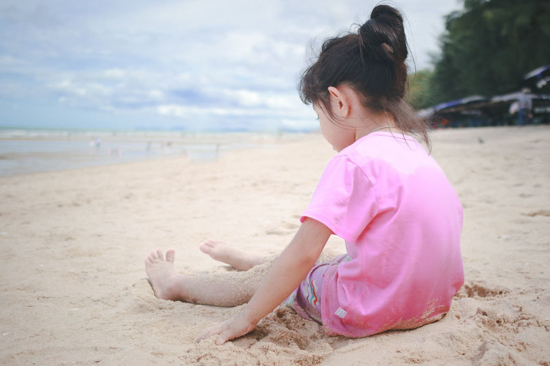 Side view of a girl sitting on beach