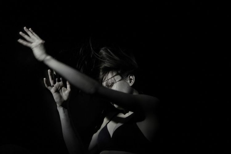 Seductive Woman Gesturing Over Black Background
