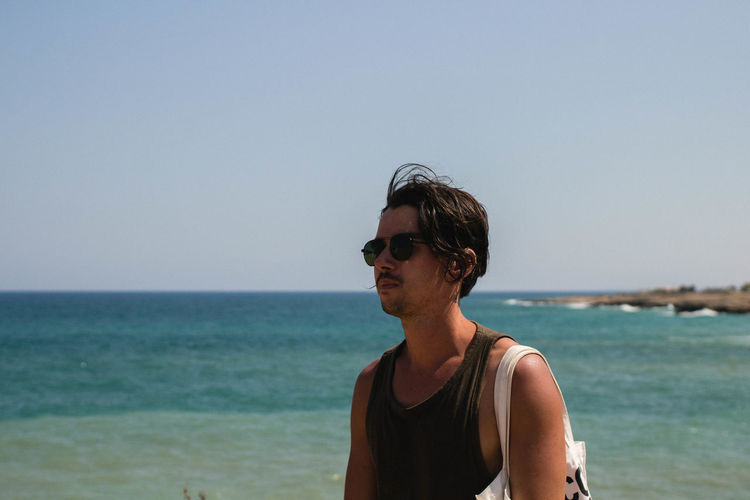 Man Wearing Sunglasses While Standing At Beach Against Clear Sky