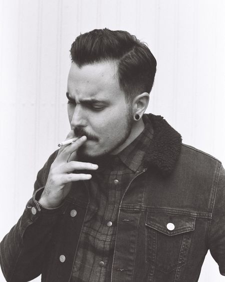 Young man smoking against wall