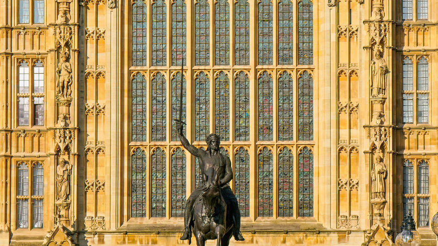 A monument of a man riding a horse infront of the Palace of Westminster in London Architecture Built Structure Building Exterior Travel Destinations Sculpture History Palace Of Westminster London Palace Building City Destinations Landmark