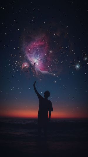 Silhouette man with hand raised standing at beach against star field