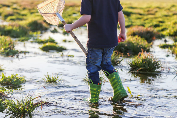 Boy Child Close-up Focus On Foreground Holding Net One Person Rain Boots Rainboots Water