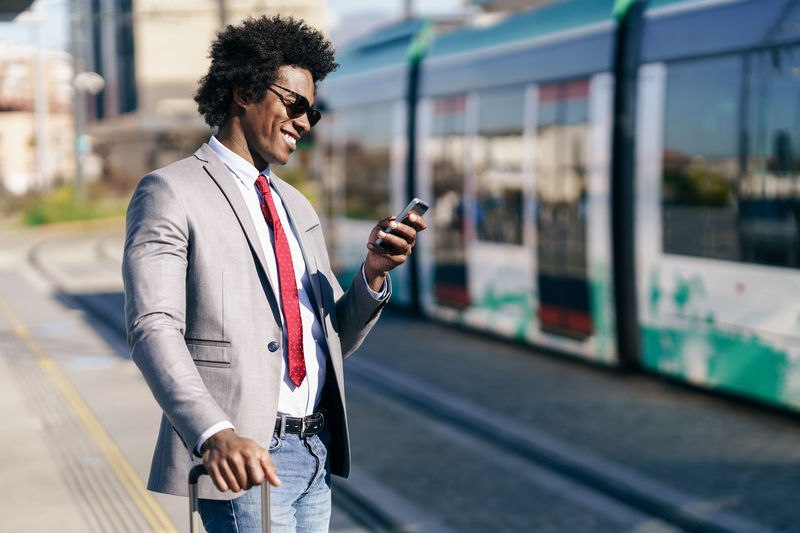 Young man using mobile phone while standing at railroad station