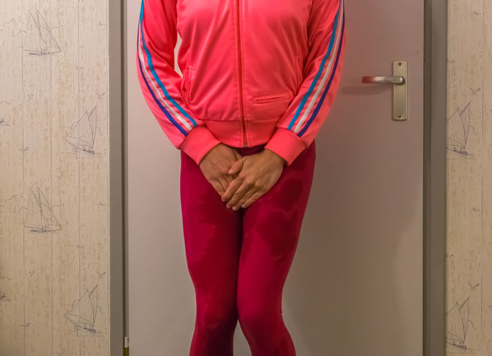 Midsection of woman with wet leggings standing against door