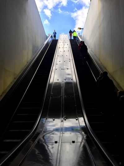 People traveling on escalator against sky