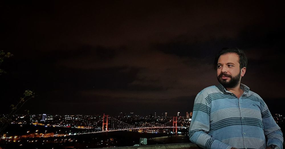 Smiling bearded man standing against illuminated cityscape at night