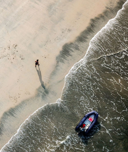 High angle view of man walking on shore at beach