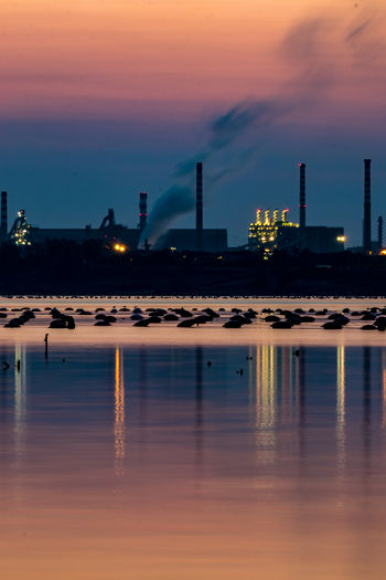 Reflection of factory in sea against sky at dusk