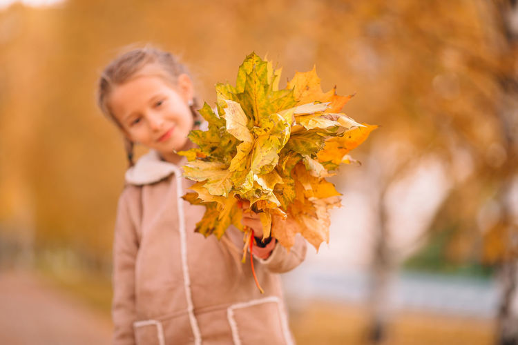Close-up of woman holding autumn leaves