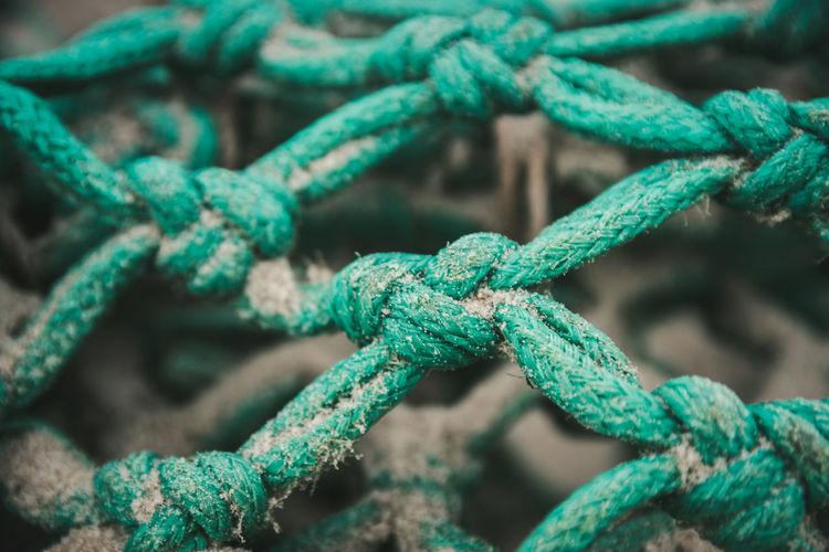 Full frame shot of sand on blue fishing net