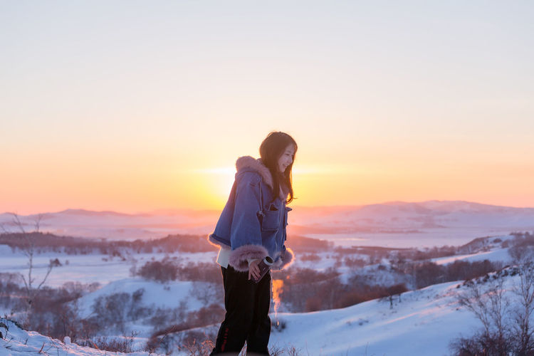 Woman standing on snow covered landscape against sky during sunset