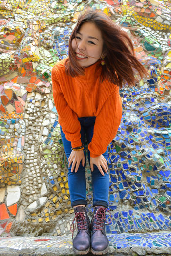 Portrait of smiling young woman bending against mosaic