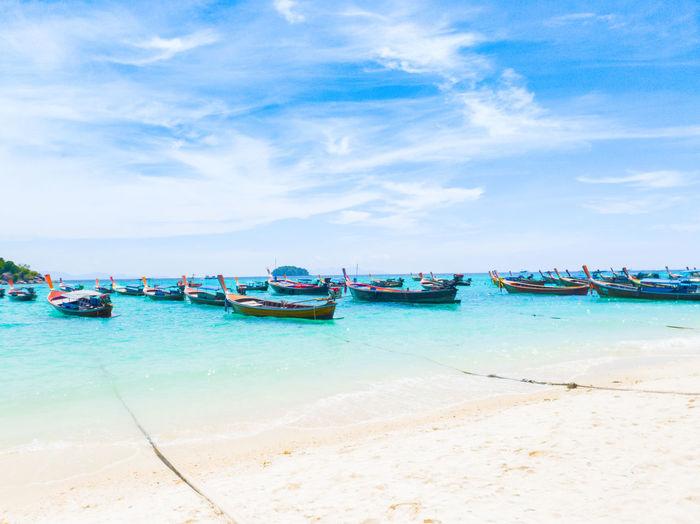 Boats moored on beach against blue sky