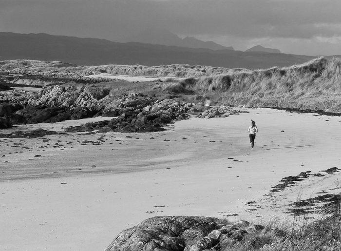 Distant View Of Woman Jogging At Beach