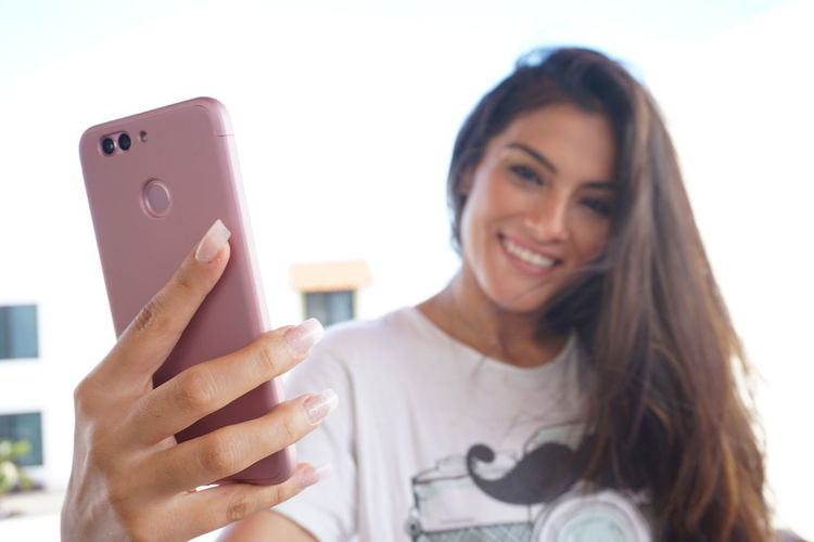 Portrait of smiling young woman using smart phone