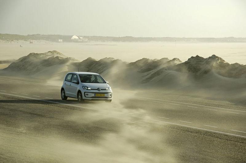 Car on road in desert against sky