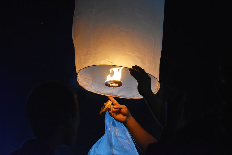 Friends igniting paper lantern at night