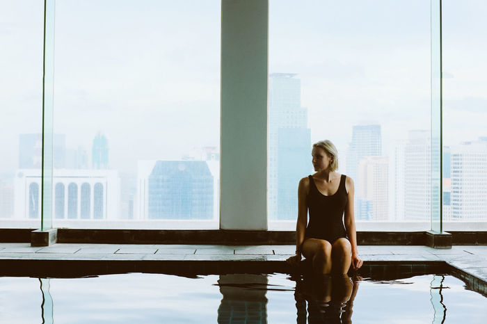 Young woman at the swimming pool with the city skyline in the background Adult Adults Only Business Businesswoman City Cityscape Day Lifestyles One Person One Woman Only One Young Woman Only Only Women Outdoors People Pool Poolside Skyscraper Skyscrapers Urban Skyline Window Women Young Adult Young Women