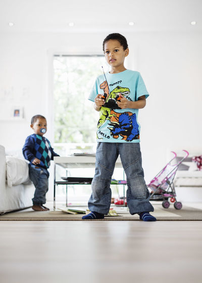 Full length of boy with toy standing on floor at home