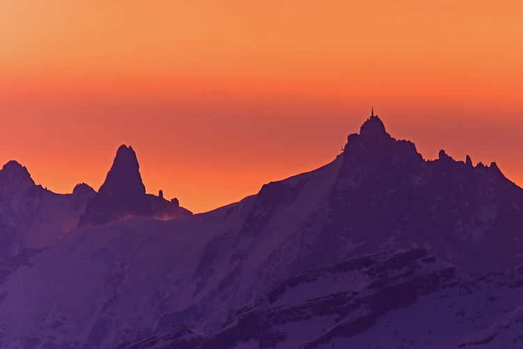 Scenic view of snow covered mountains against orange sky
