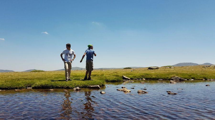 Men standing on lake against sky