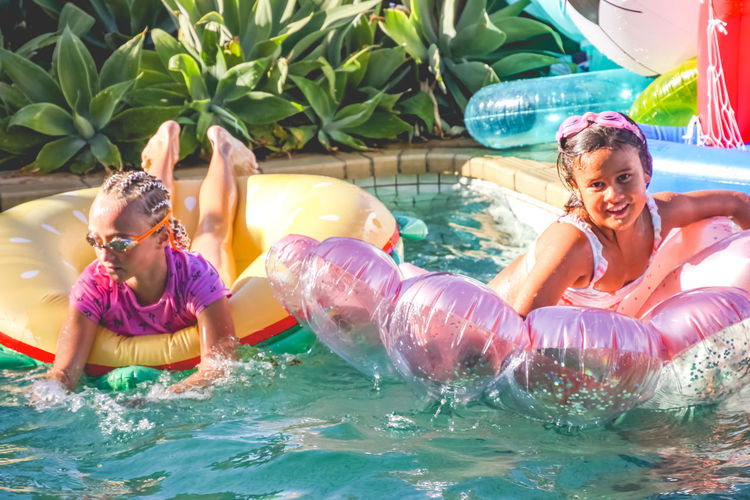 young girls having fun in the pool with inflatables Water Child Childhood Leisure Activity Pool Swimming Pool Girls Lifestyles Real People Females Enjoyment Fun Holiday Day Inflatable  Vacations Floating On Water Daughter Outdoors Inflatable  Diversity