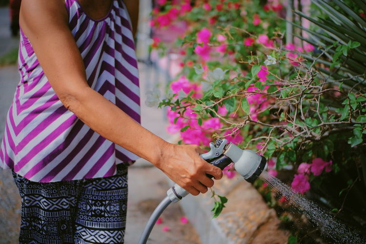 Midsection of woman watering plants
