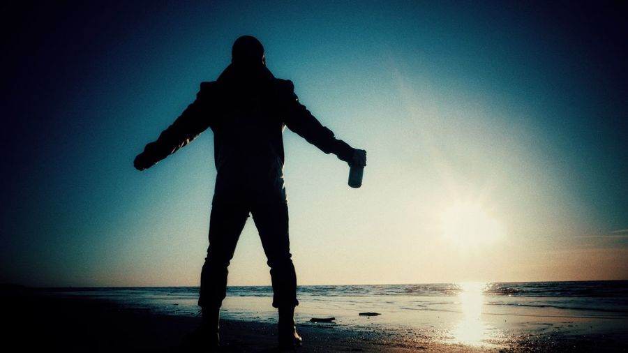 Silhouette man standing on beach against bright sun