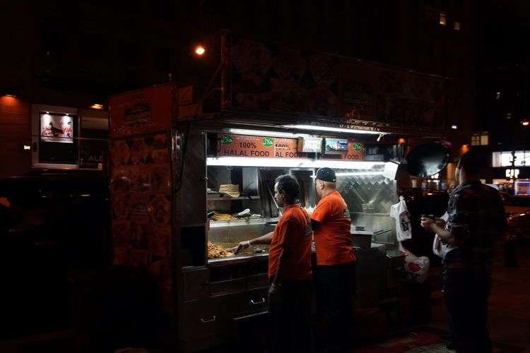 Cities At Night City City Life Hot Dog Stand Hungry Illuminated Lifestyles New York City Store Streetphotography Original Experiences eating indian streetfood by night in new york city....an original experience People And Places Connected By Travel Mobility In Mega Cities HUAWEI Photo Award: After Dark