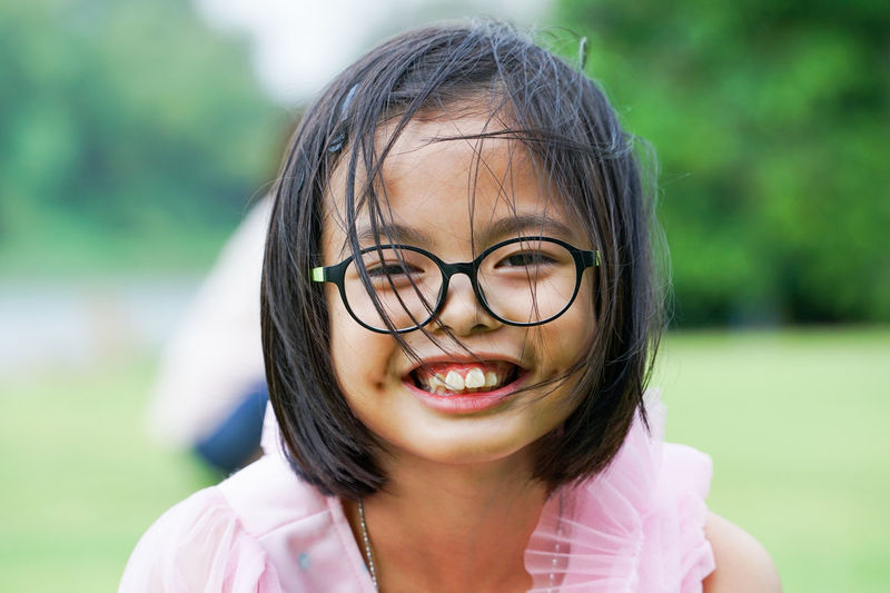 Closeup smiling face of asian girl looking at the camera with blurred natural background