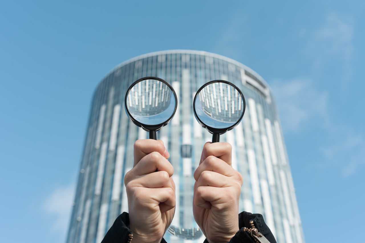 Close-Up Of Hand Holding Magnifying Glass Against Building