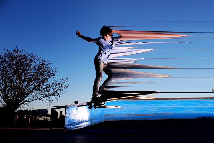 Digital composite image of teenage boy skateboarding in mid-air against clear blue sky