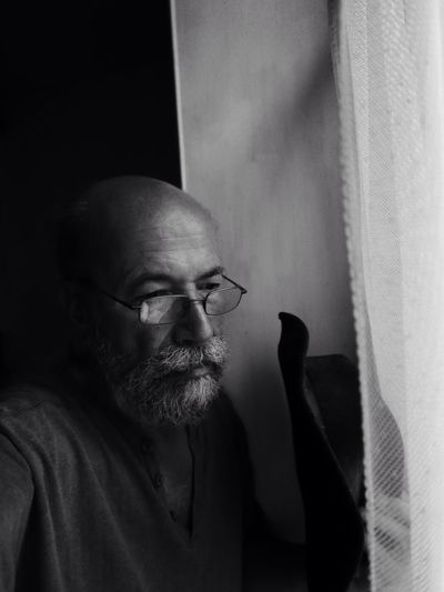 Thoughtful Senior Man Wearing Eyeglasses Holding Hat While Standing By Window