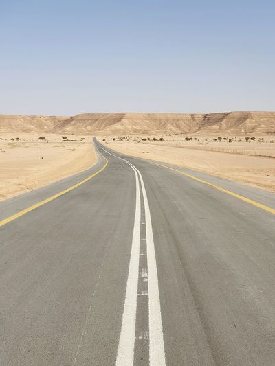 Empty road amidst desert against clear sky