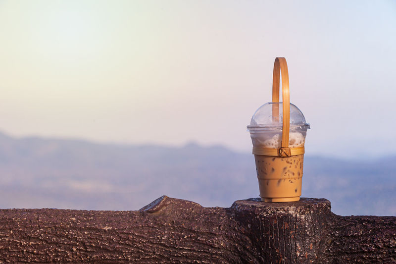 Close-up of drink on table against sky