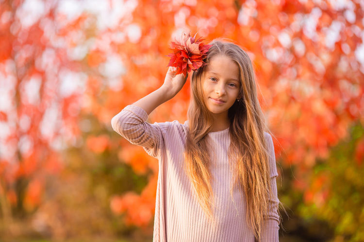 Portrait of girl standing against plants during autumn