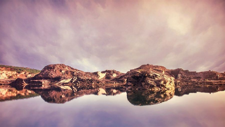 Rock formations reflecting on calm lake against cloudy sky